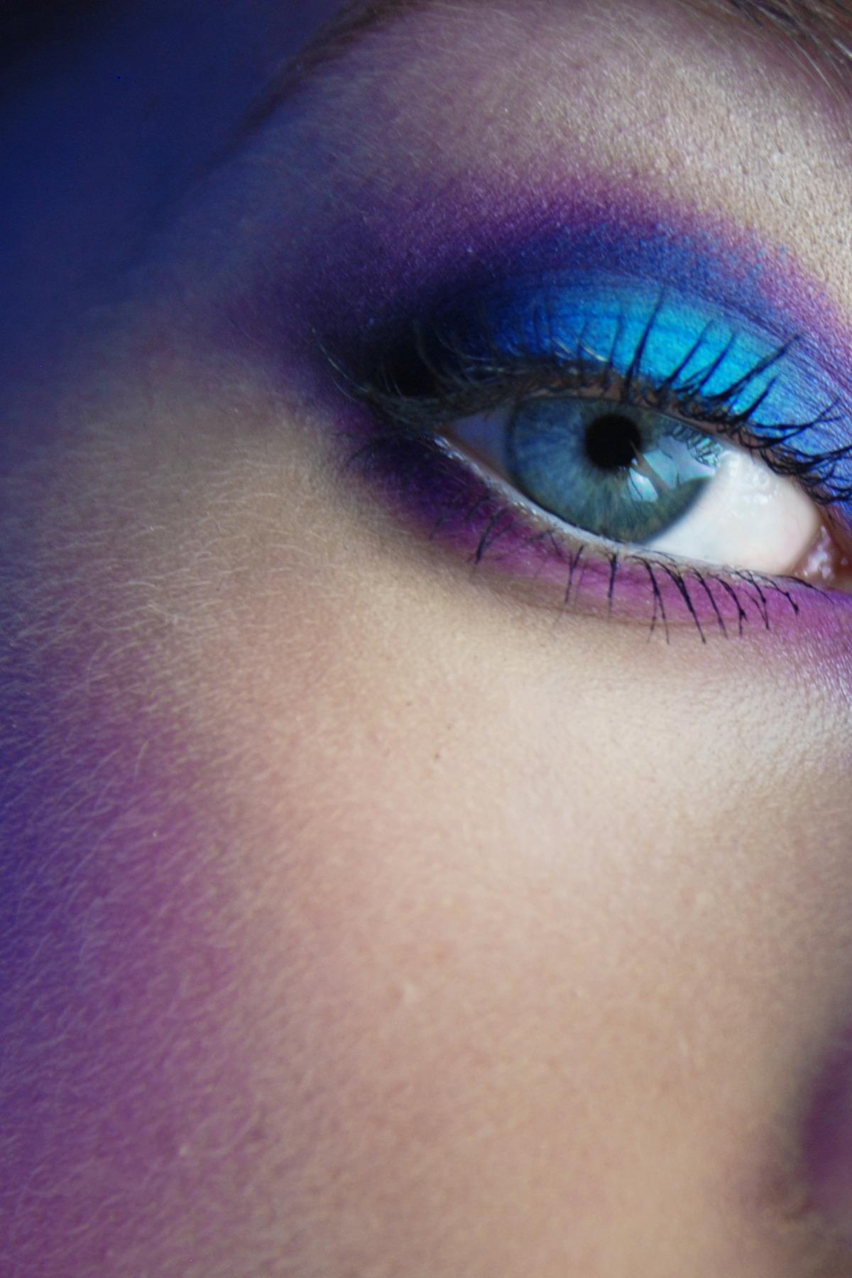 Zdjęcie przedstawia zbliżenie na oko kobiety, pomalowane na niebiesko-fioletowo.