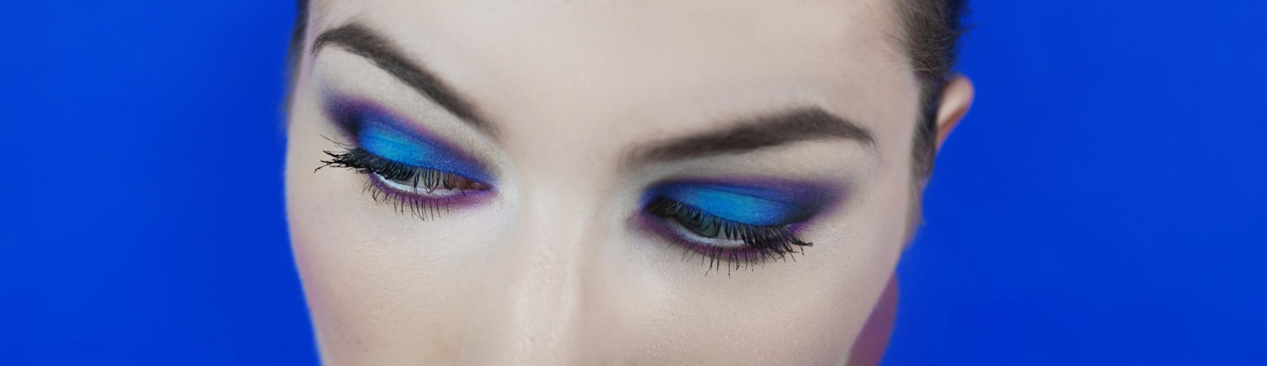 Zdjęcie przedstawia oczy młodej kobiety w makijażu, na niebieskim tle, patrzące w prawą stronę.