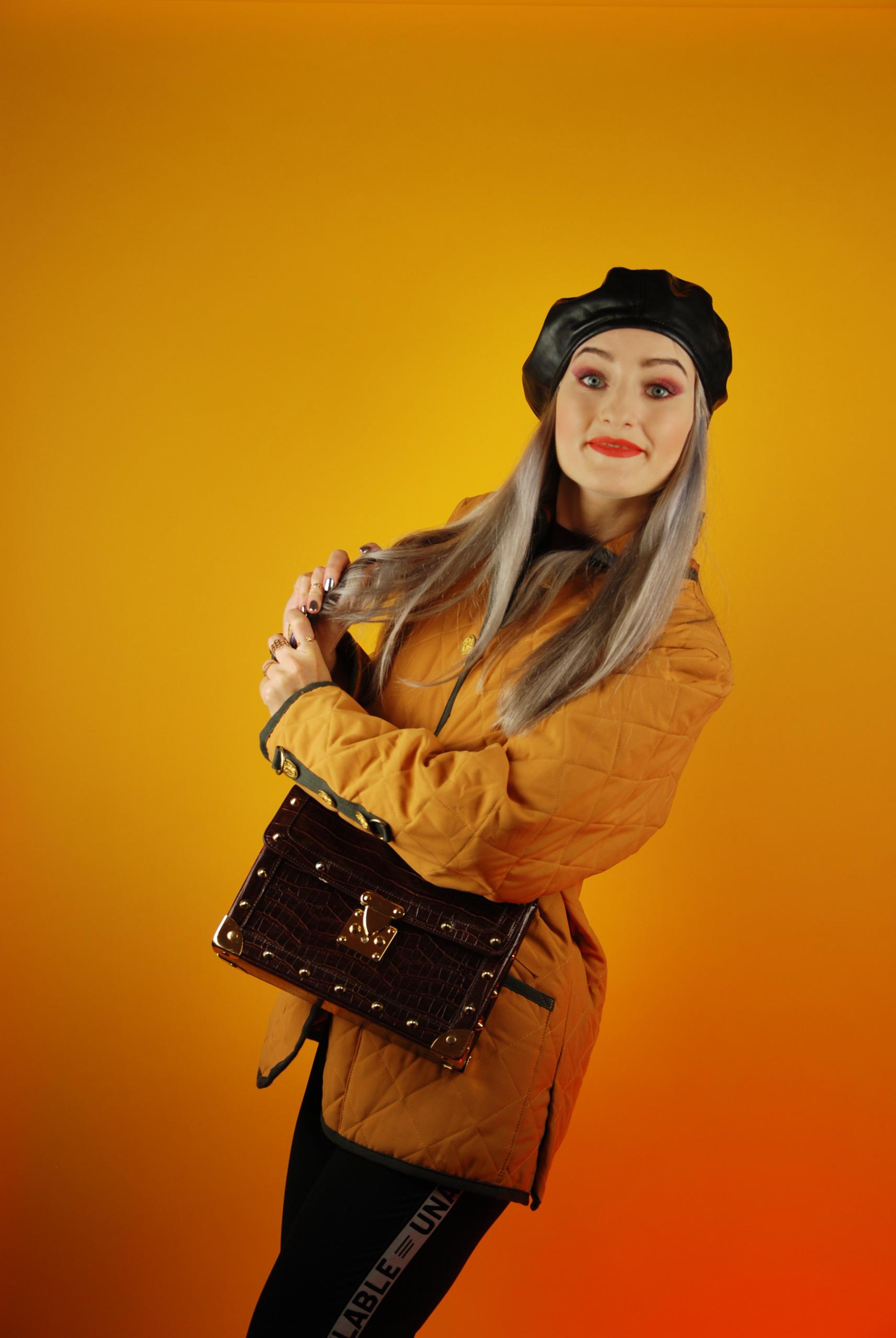 Zdjęcie przedstawia młodą, uśmiechniętą kobietę ubraną w żółtą pikowaną kurtkę. Kobieta ma czarny beret na głowie, brązową torebkę i jasnoszare włosy, całość na żółtym tle.