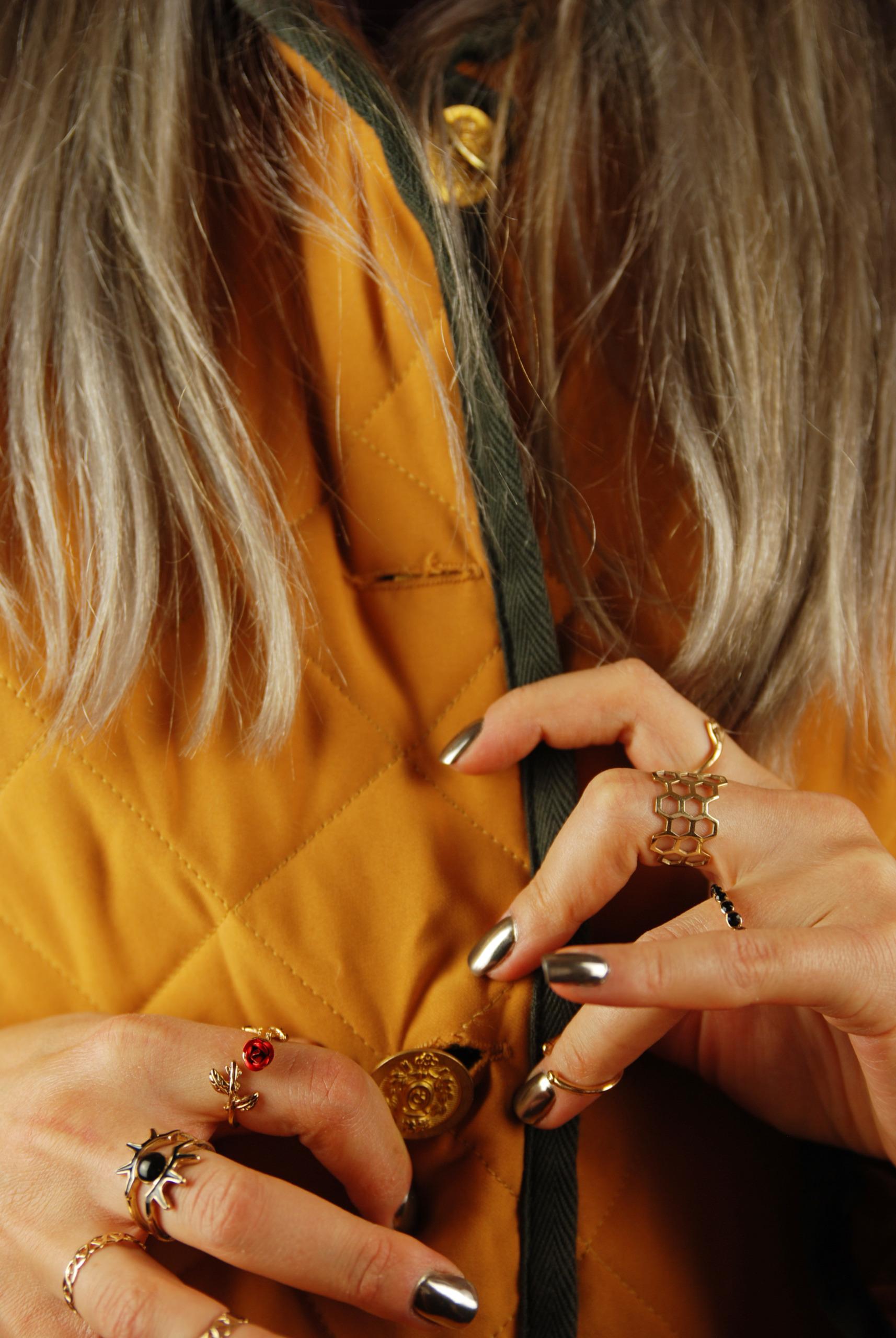 Zdjęcie przedstawia zbliżenie na dłonie zapinające złote guziki żółtej kurtki. Na dłoniach jest dużo złotych pierścionków, a paznokcie są koloru srebrnego, widać też szare włosy.