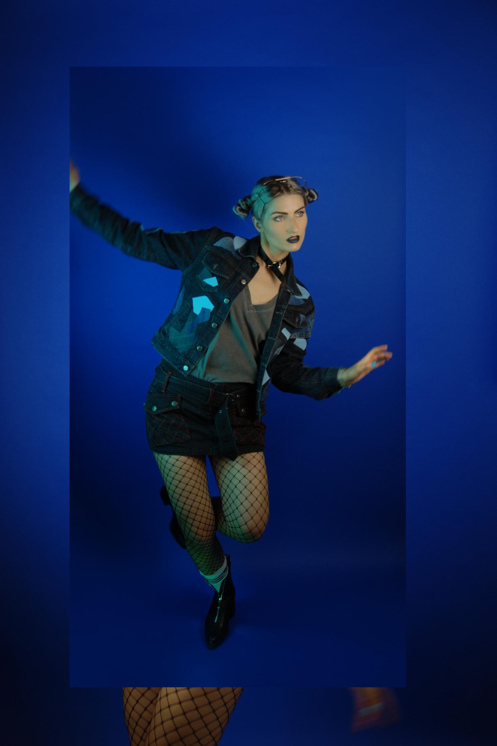 Zdjęcie przedstawia młodą kobietę w tanecznej pozie na niebieskim tle, kobieta ubrana jest w krótką spódniczkę, kurtkę, białe skarpety, czarne buty, włosy ma zebrane w dwa koczki, a usta pomalowane na ciemny kolor.