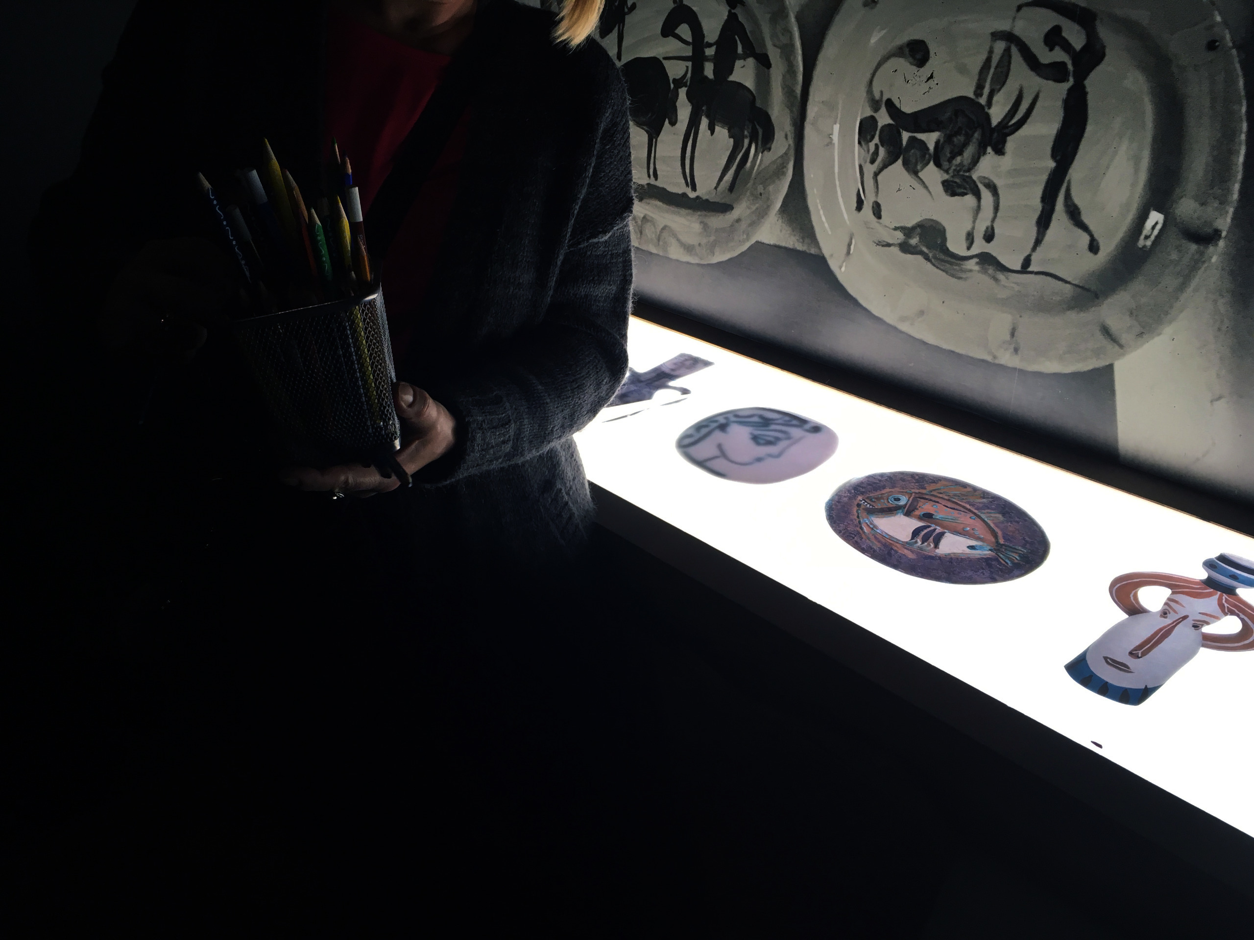 Zdjęcie jest mocno zaciemnione, widzimy dłoń trzymającą kubek z kredkami, w tle mocne światło.