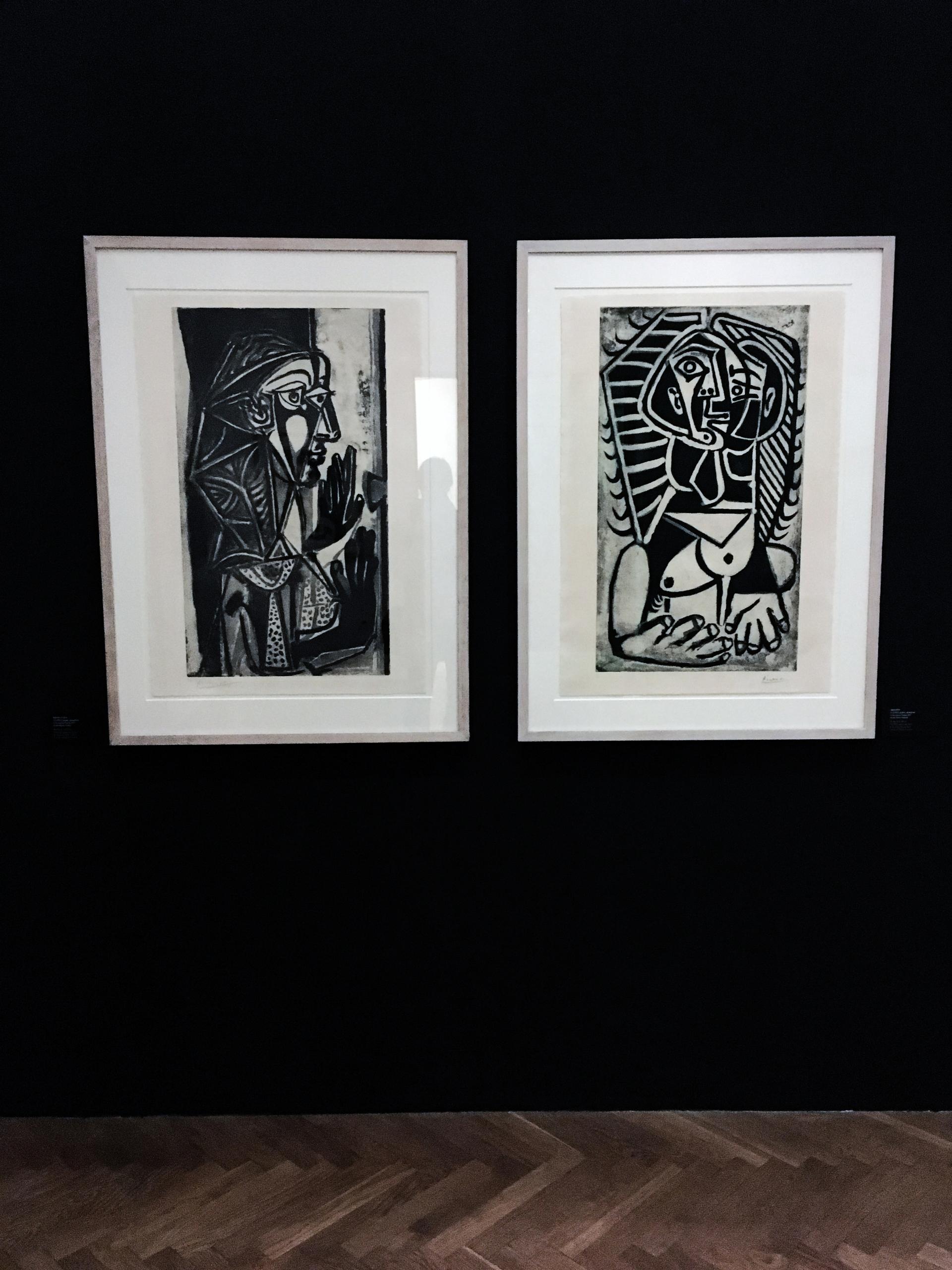 Zdjęcie przedstawia dwie prace wykonane w technice graficznej, powieszone na czarnej ścianie.