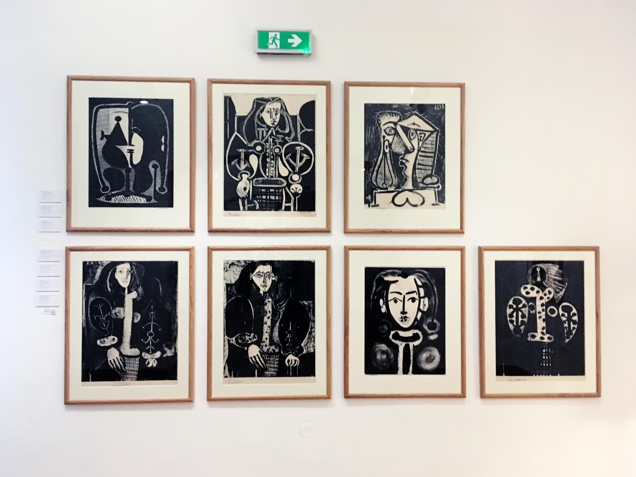 Zdjęcie przedstawia serię siedmiu prac wykonanych w technice graficznej, zawieszonych na białej ścianie.