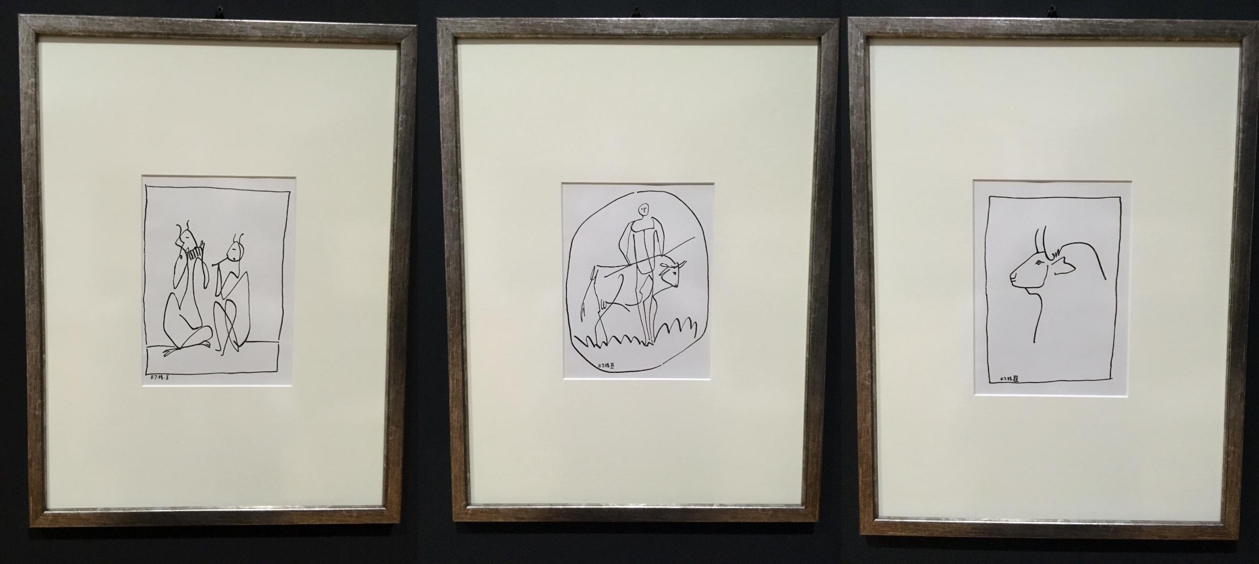 Zdjęcie przedstawia trzy rysunki oprawione w ramki, na których widzimy ludzi grających na instrumentach, człowieka z bykiem i byka.