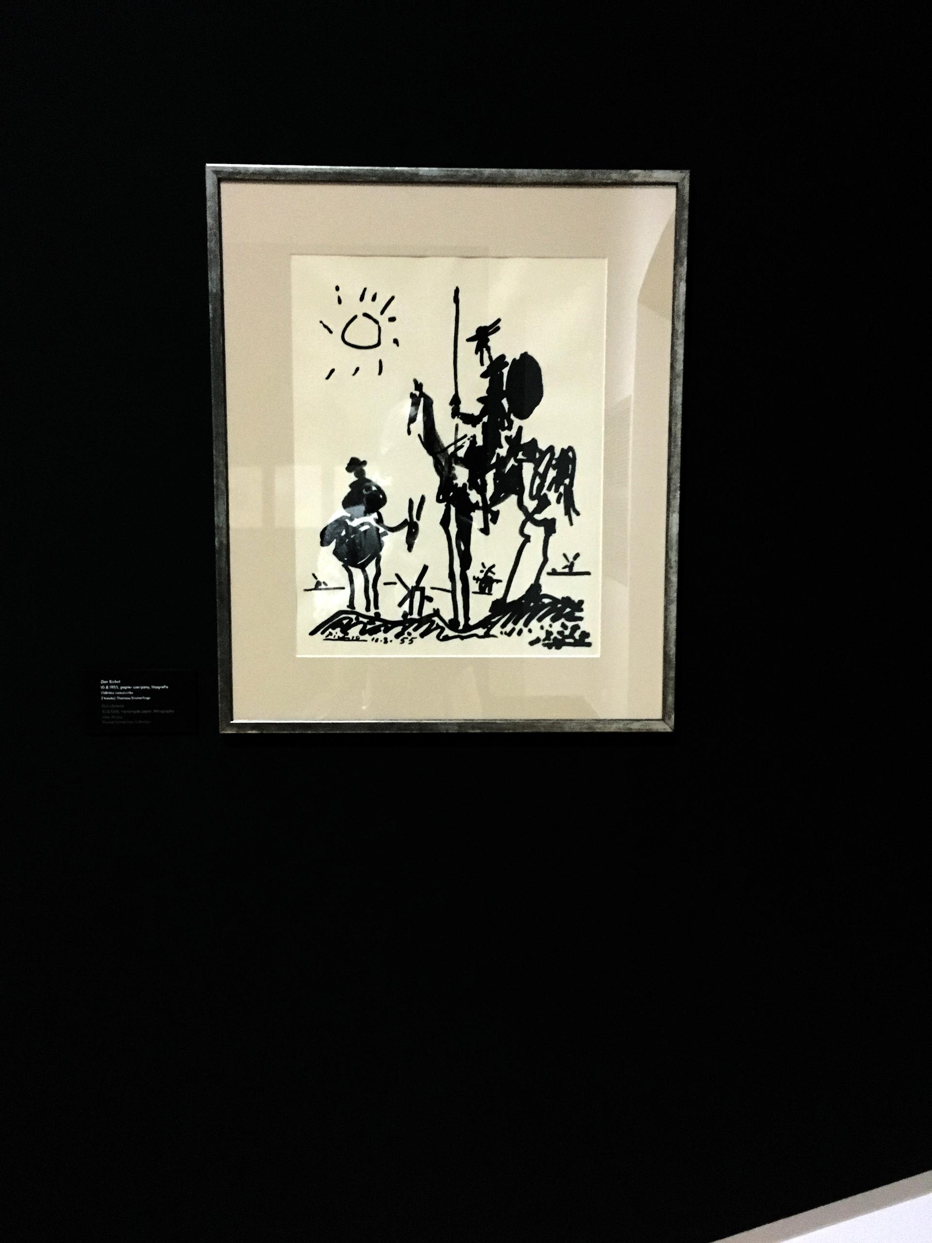 Zdjęcie przedstawia pracę znanego artysty Pabla Picassa zawieszoną na czarnej ścianie.