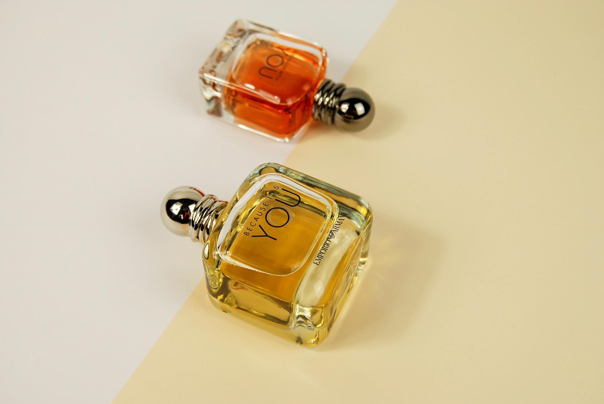 Zdjęcie przedstawia flakony perfum leżące na jasnym podłożu, kadr zdjęcia przebiega po skosie.