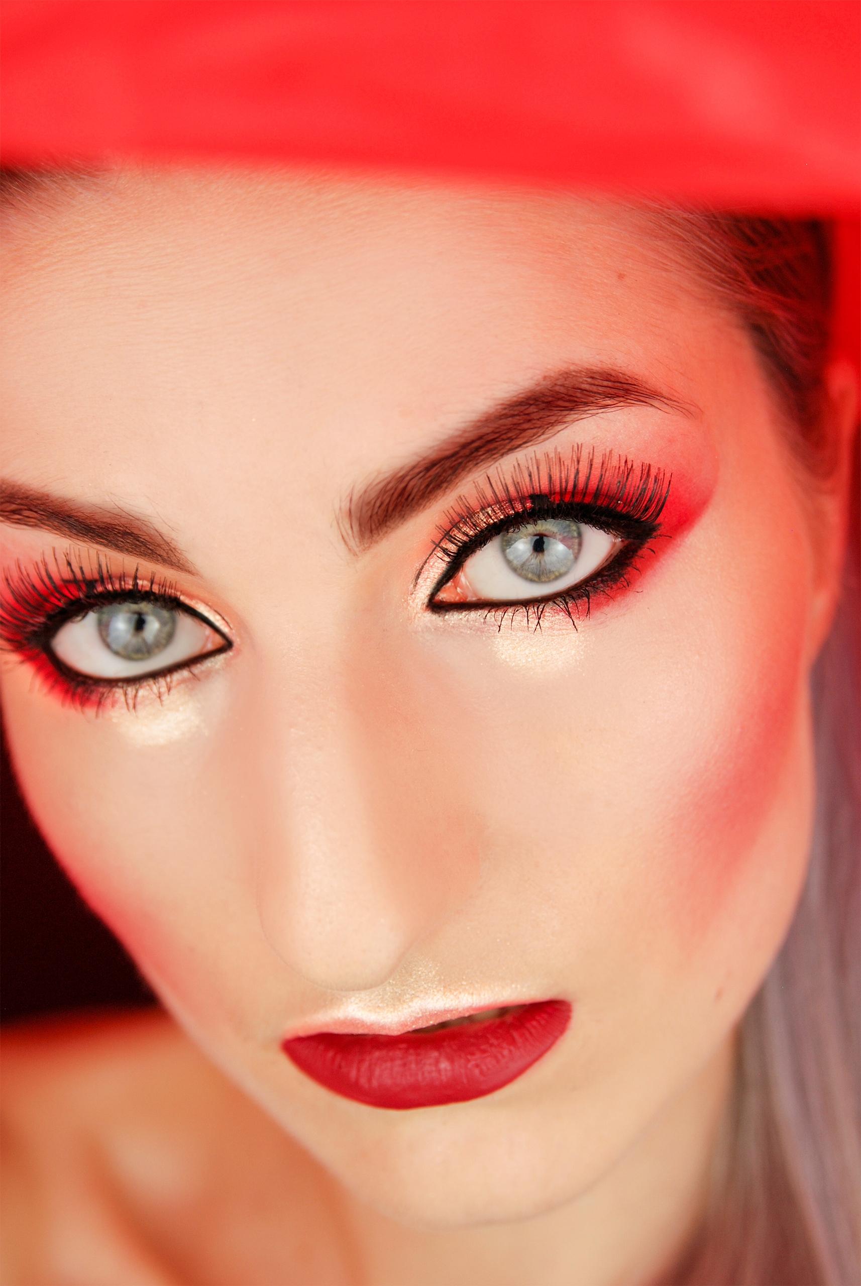 Zdjęcie przedstawia twarz kobiety w mocnym makijażu i czerwonym świetle.