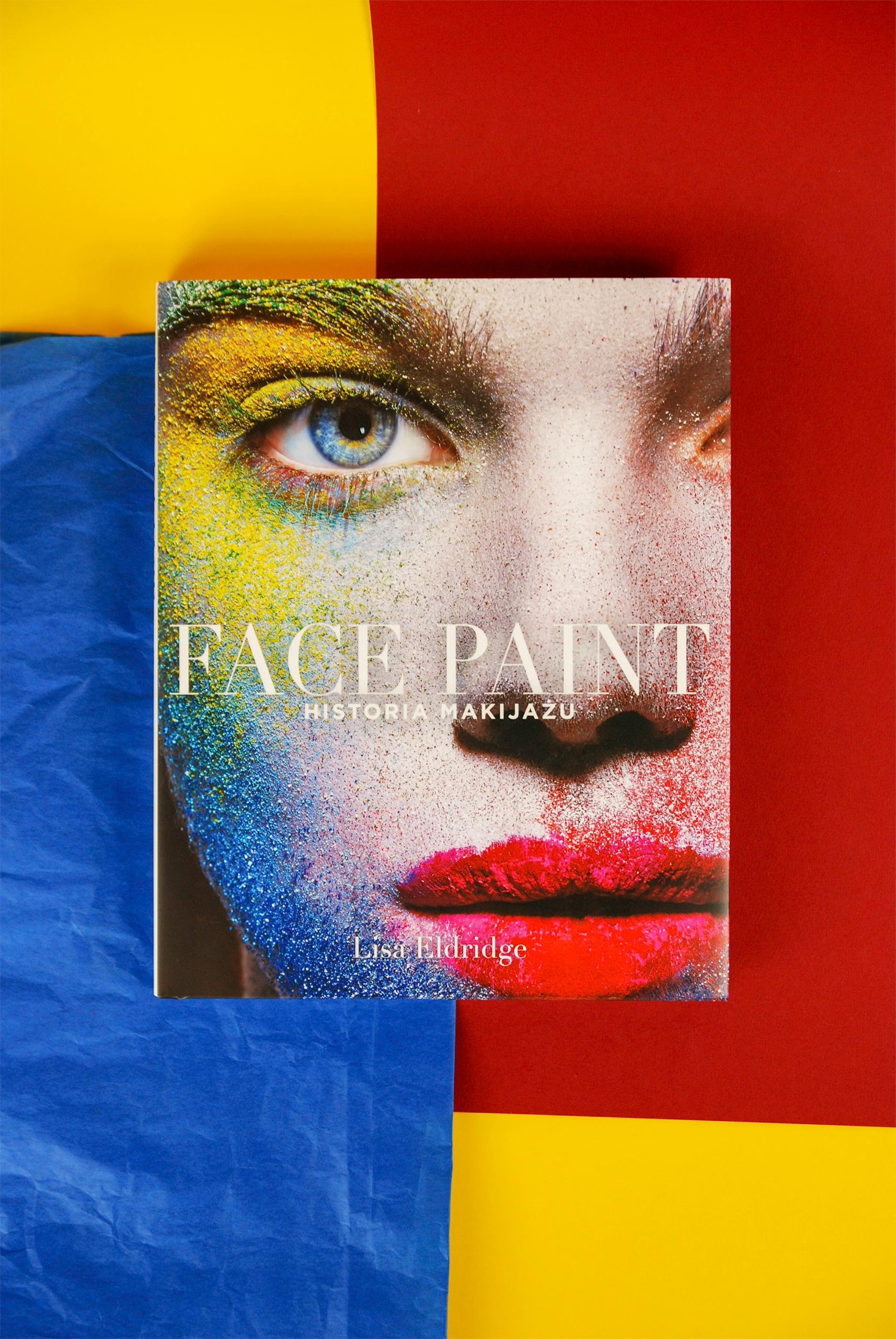 Zdjęcie przedstawia okładkę książki sfotografowaną od góry. Dookoła kolorowe papiery w kolorze czerwonym, niebieskim i żółtym.