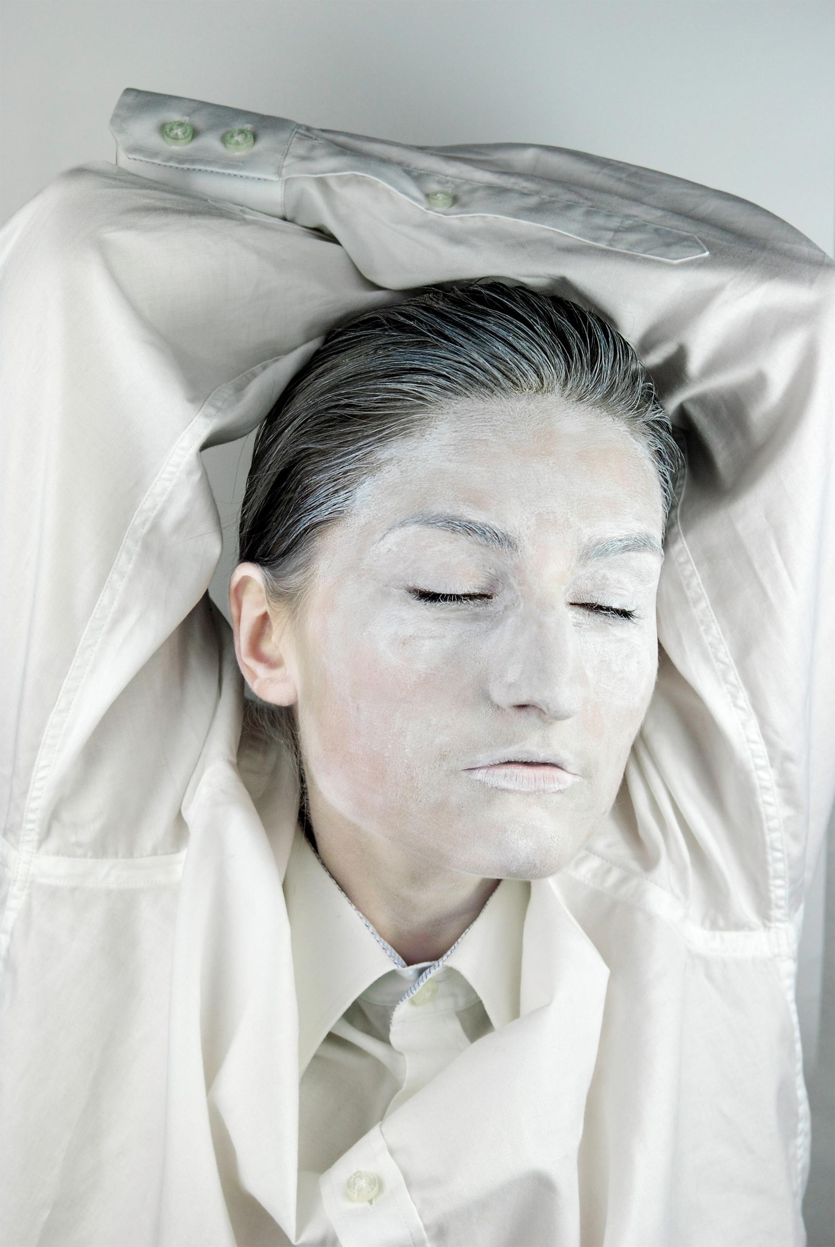 Zdjęcie przedstawia postać pomalowaną na biało z zamkniętymi oczami i rękami podniesionymi do góry.