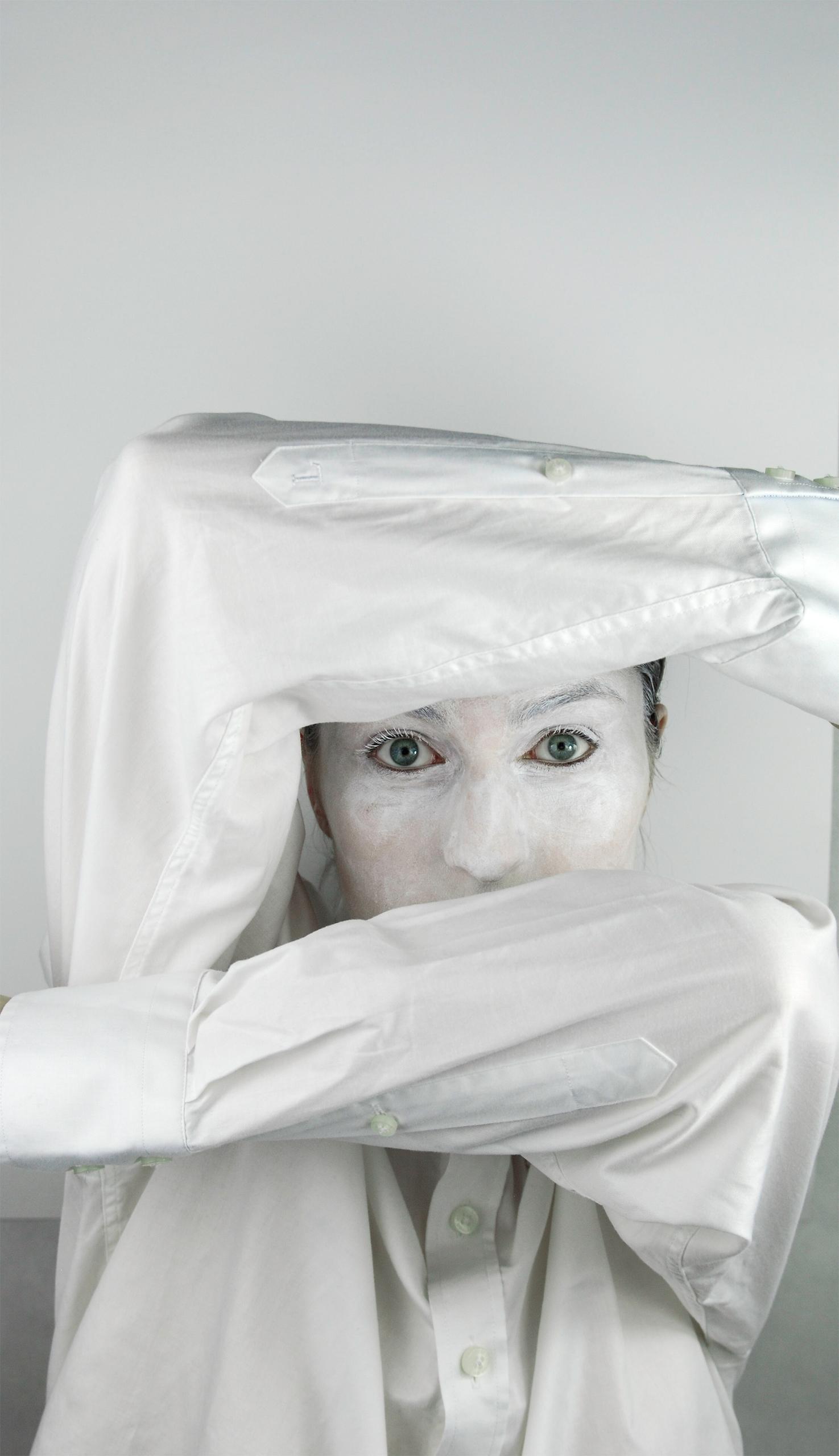 Zdjęcie przedstawia postać pomalowaną na biało, która zasłania twarz rękami w białej koszuli.