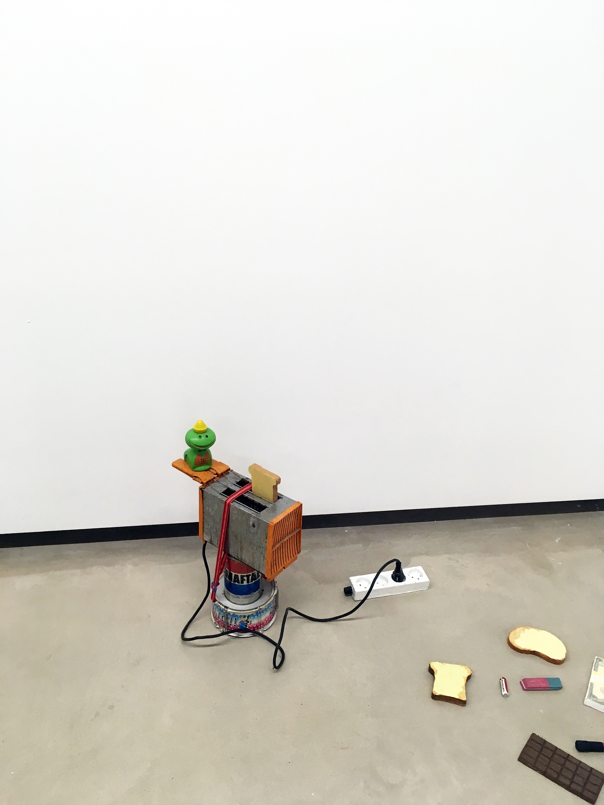 Zdjęcie przedstawia różne przedmioty ułożone obok siebie na podłodze, wszystko na tle białej ściany.