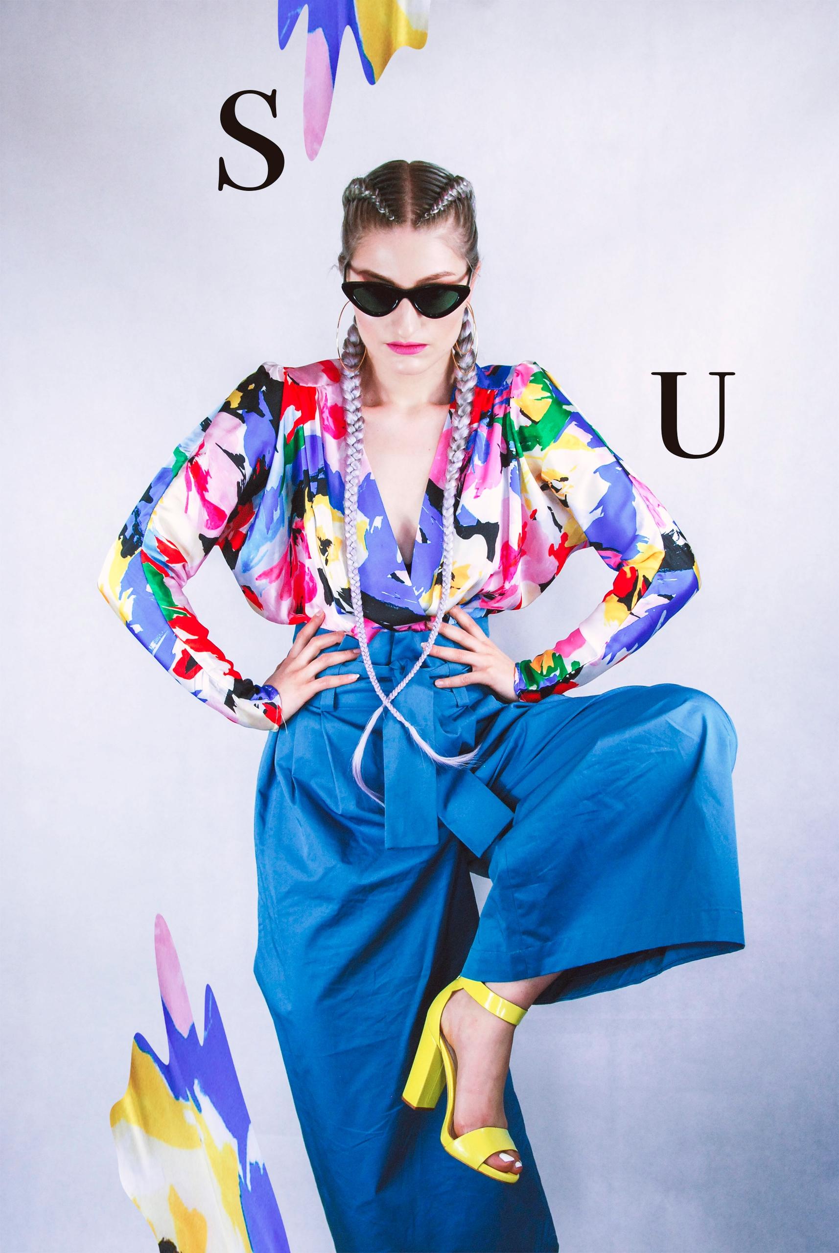 Zdjęcie przedstawia sylwetkę kobiety w niebieskich spodniach, kolorowej bluzce. Kobieta podnosi nogę do góry, widzimy jej żółty but. Na zdjęciu widnieje czarny napis i graficzne elementy.
