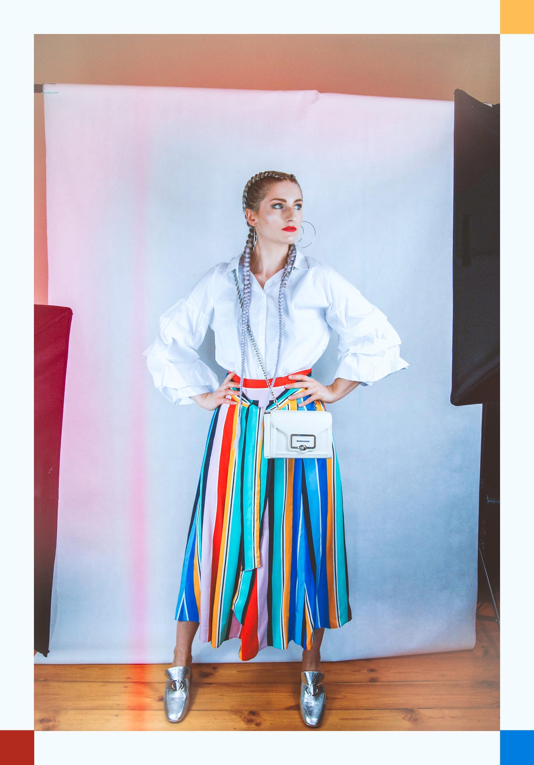 Zdjęcie przedstawia sylwetkę kobiety w kolorowej spódnicy i białej bluzce. Kobieta ma długie warkocze i srebrne buty.