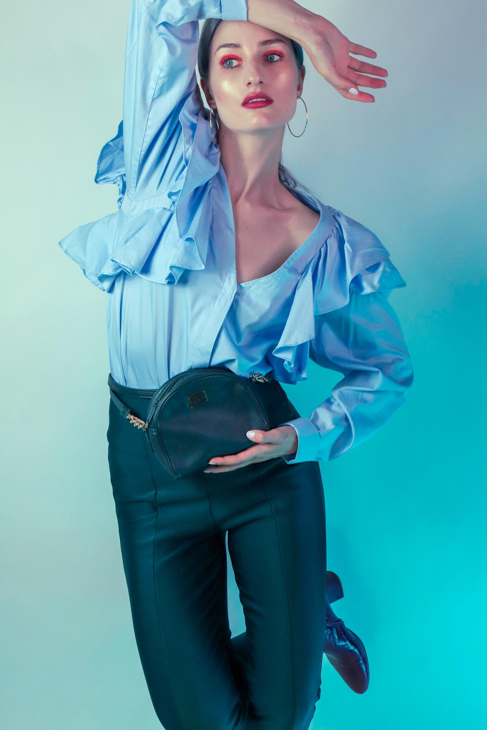 Fotografia przedstawia kobietę w nienaturalnej pozie. Kobieta patrzy w bok, w ręku trzyma torebkę i ma na sobie błękitną koszulę.