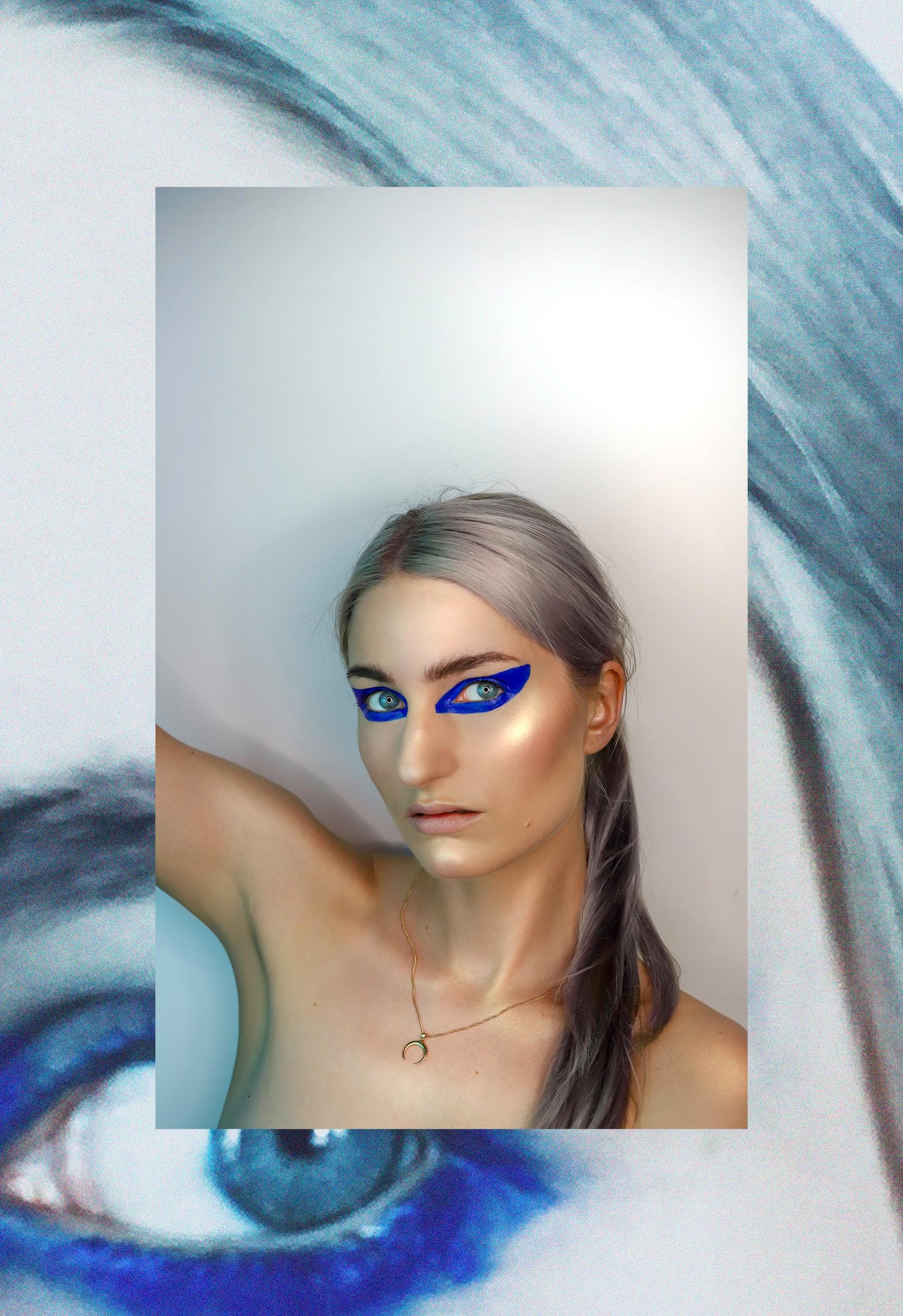 Zdjęcie przedstawia portret kobiety z szarymi włosami, w mocnym makijażu oczu. Zdjęcie w ramie.