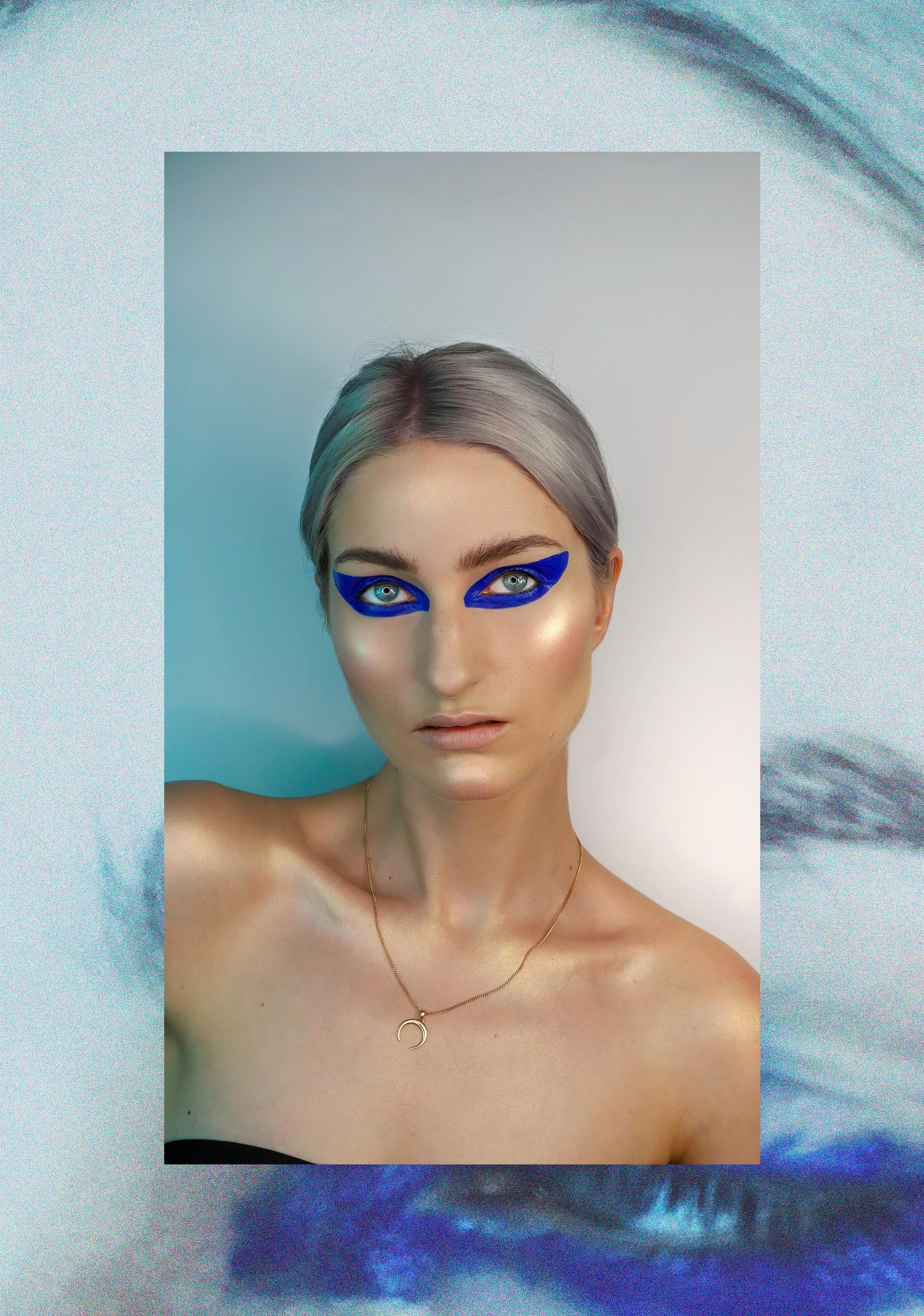 Zdjęcie przedstawia portret kobiety w mocnym makijażu oczu i złotym naszyjnikiem na szyi. Zdjęcie w ramie.