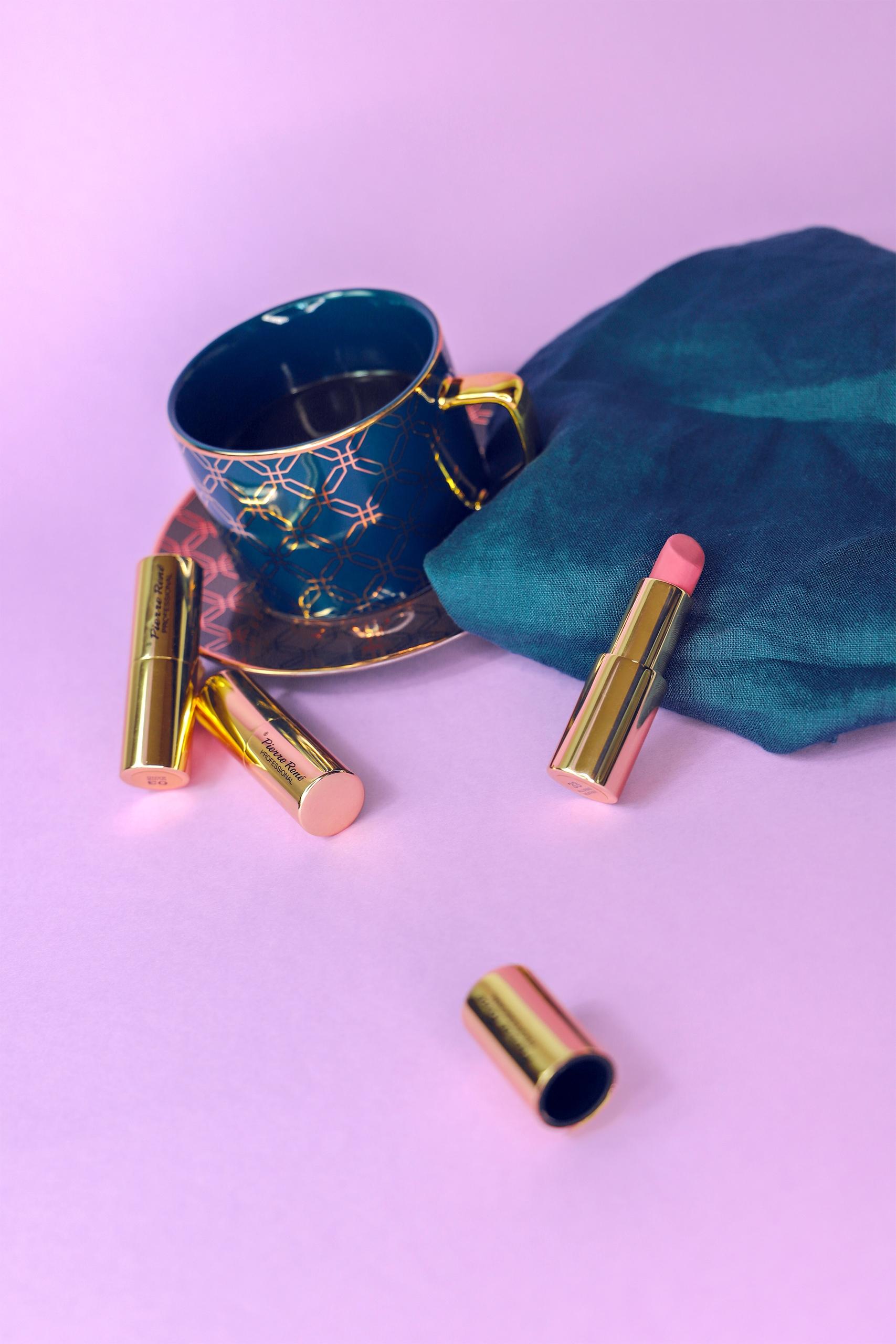 Zdjęcie przedstawia filiżankę, serwetę i złote pomadki na jasno-fioletowym tle.