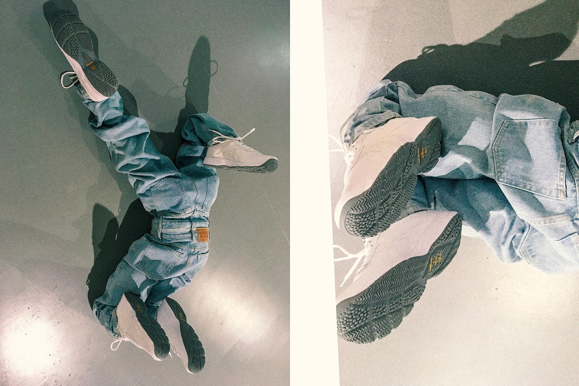 Zdjęcie przedstawia obiekt w postaci dwóch par spodni połączonych ze sobą. Widzimy białe sportowe obuwie na szarej podłodze.