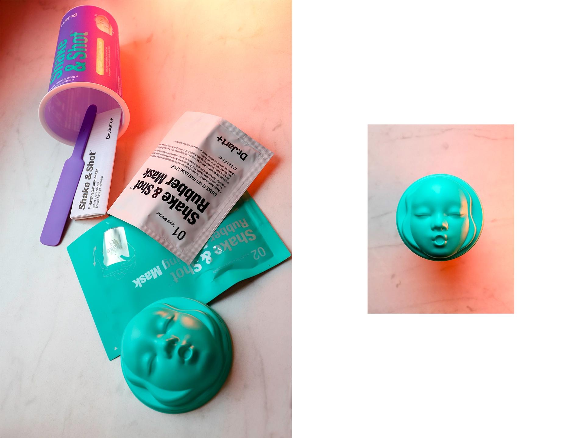 Zdjęcie przedstawia różne przedmioty rozsypane na jasnym podłożu. Widzimy fioletowy kubek i miętową zatyczkę w kształcie twarzy.