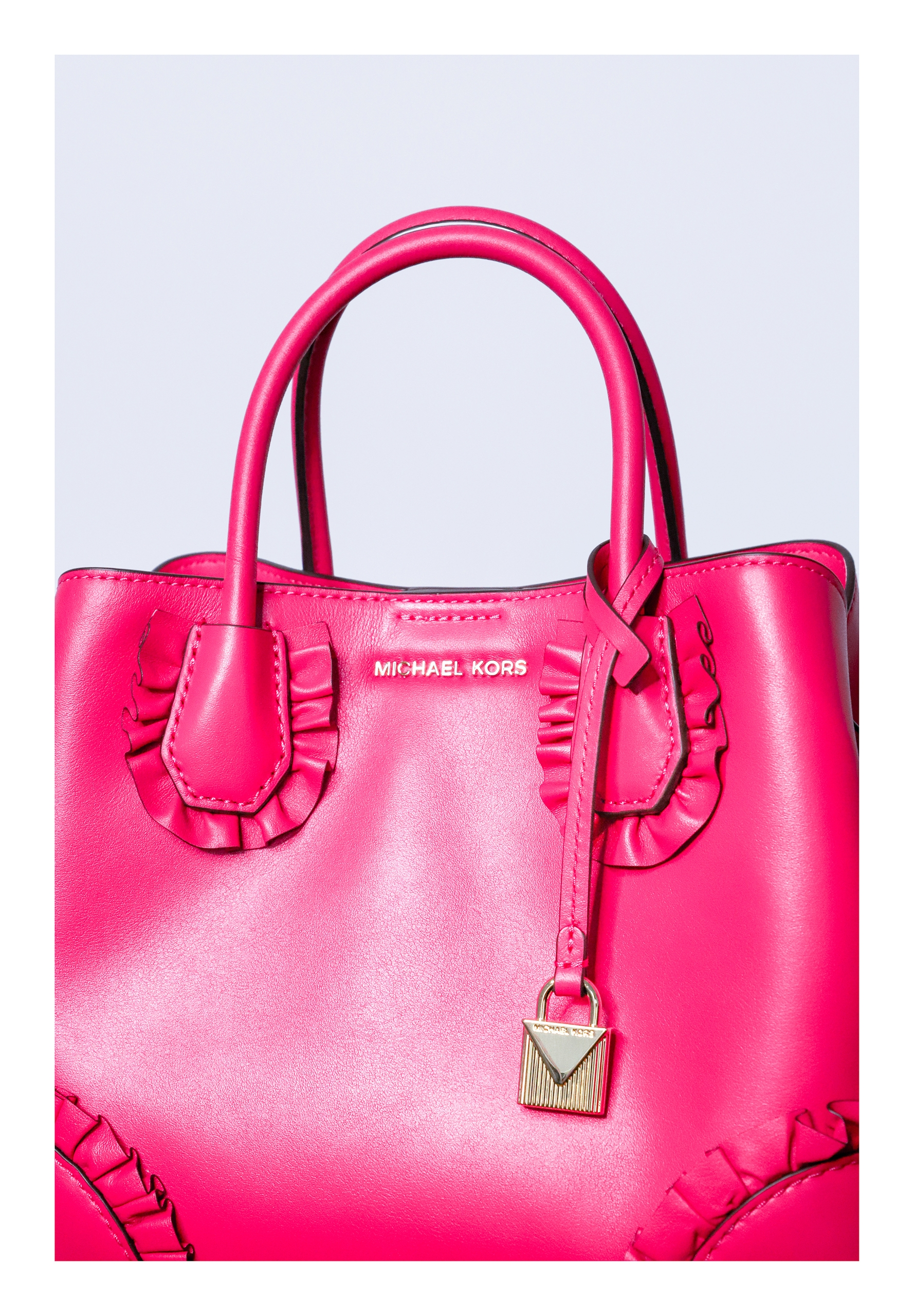 Zdjęcie przedstawia fragment różowej torebki na jasnym tle.