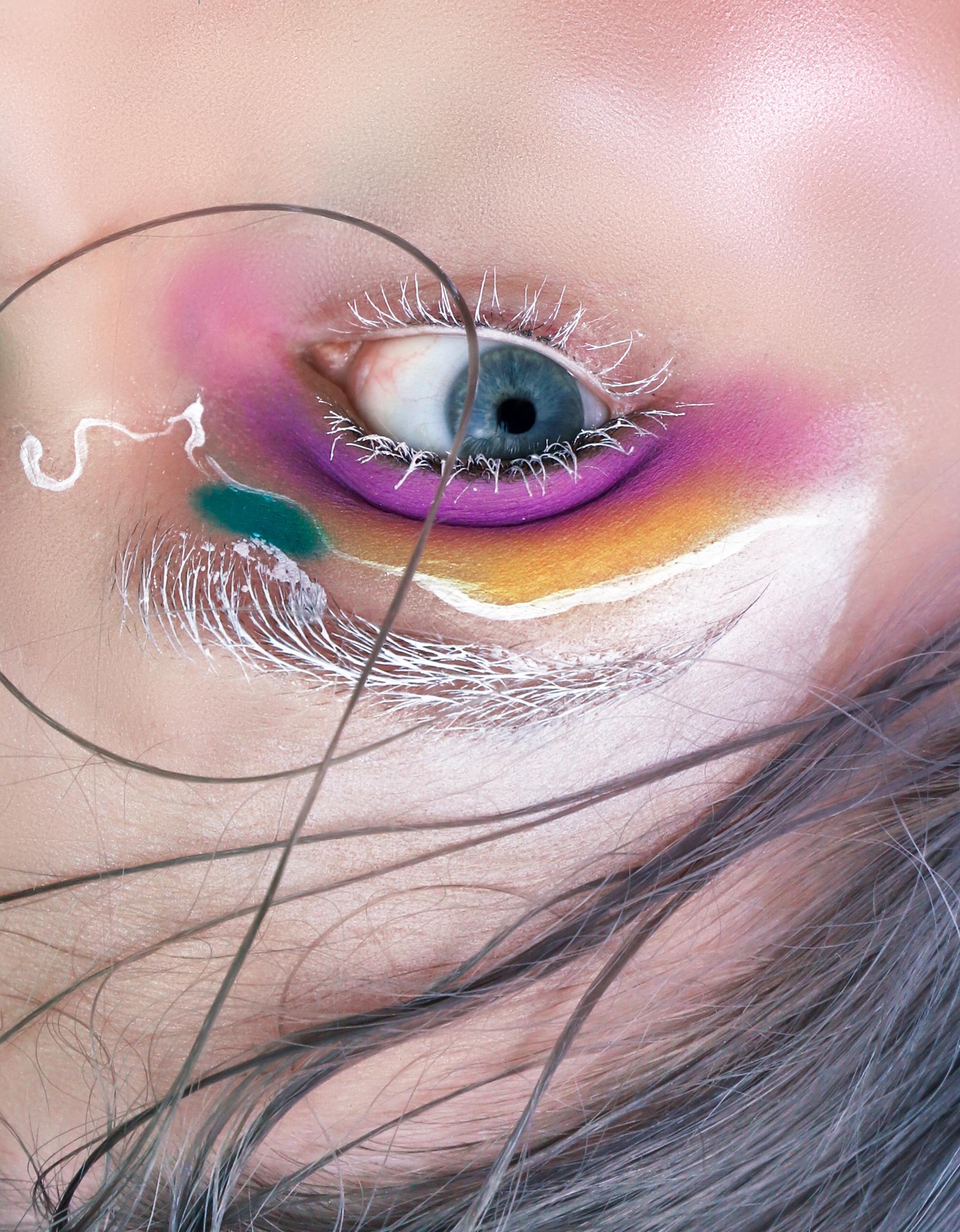 Zdjęcie przedstawia odwrócone oko w powiększeniu. Na powiece widzimy kolorowy makijaż.