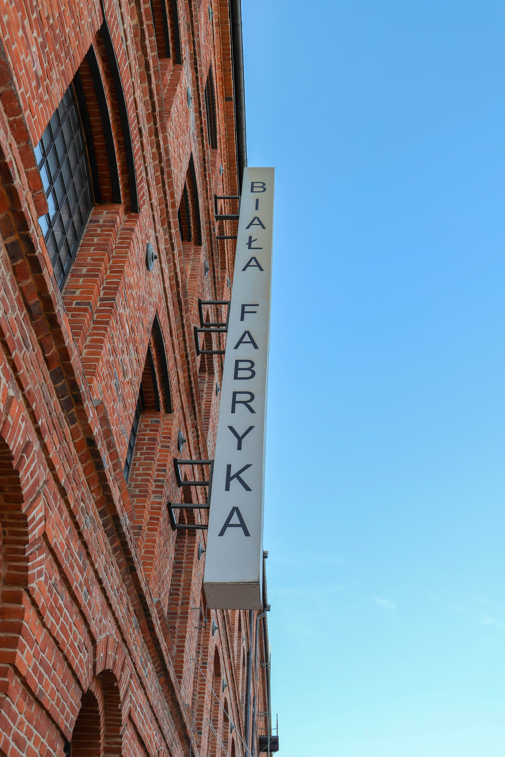 Zdjęcie przedstawia fragment budynku z cegły i niebieskie niebo.