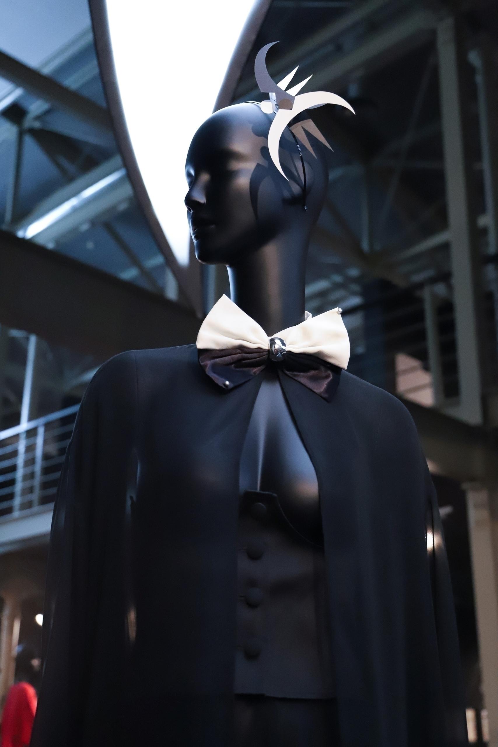 Zdjęcie przedstawia czarnego manekina sfotografowanego od dołu. Manekin ma na sobie biało-czarny strój i dziwne nakrycie głowy.