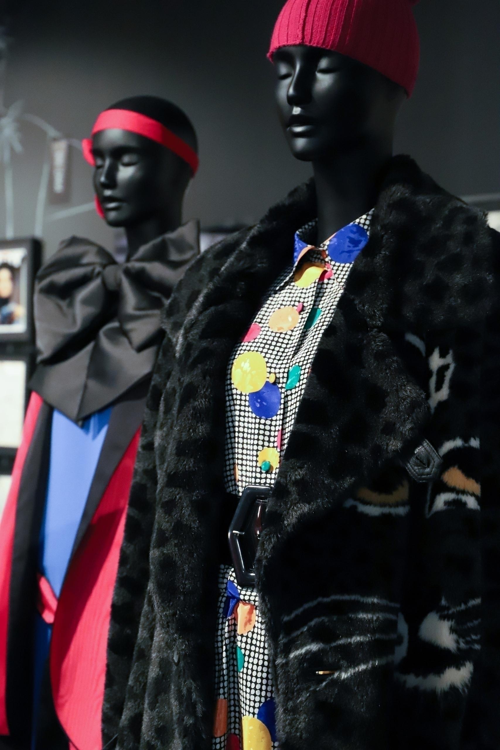 Zdjęcie przedstawia dwa czarne manekiny stojące obok siebie, manekiny ubrane są w kolorowe stroje.