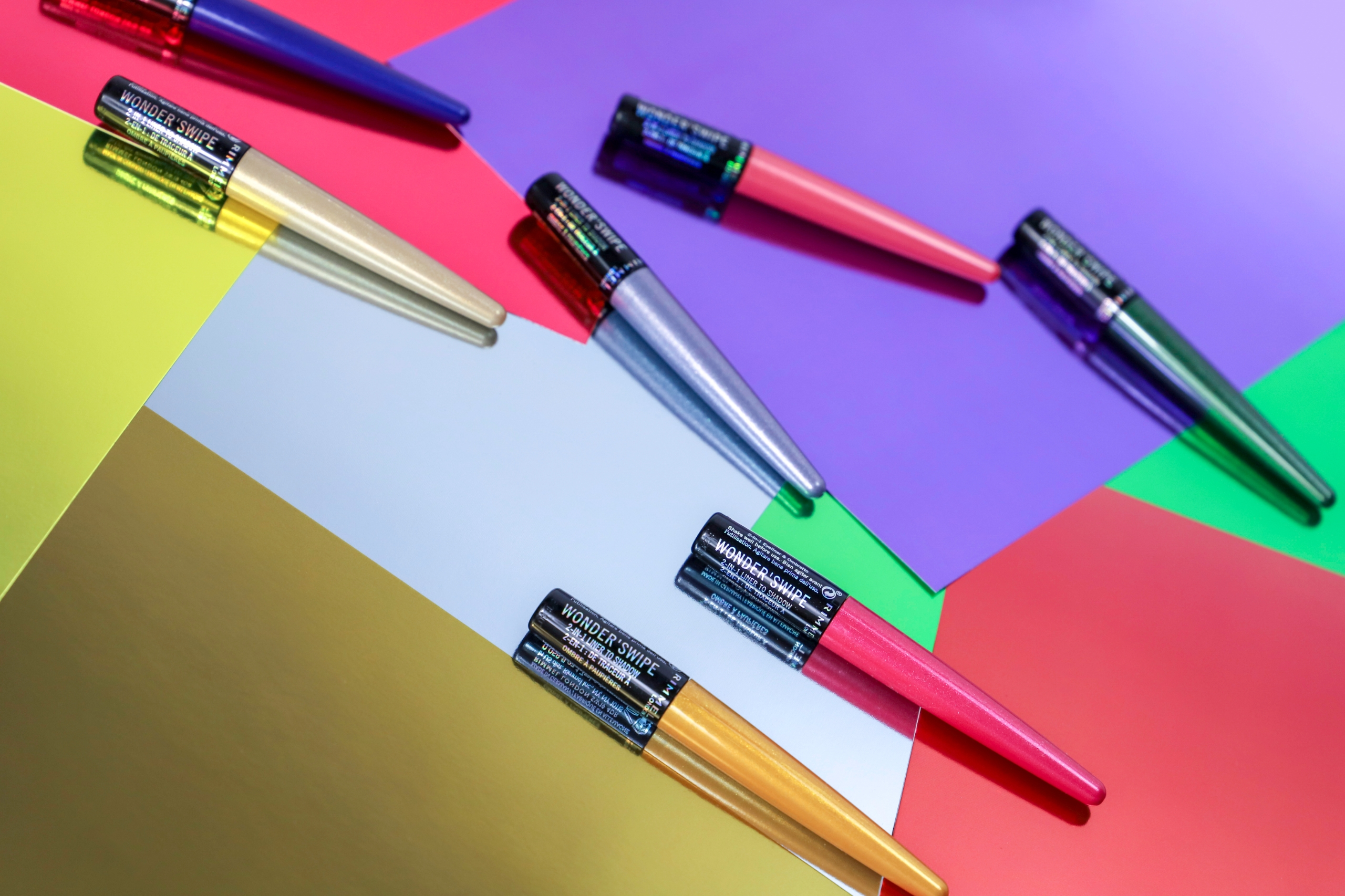 Zdjęcie przedstawia obiekty rozrzucone na kolorowych kartonach.