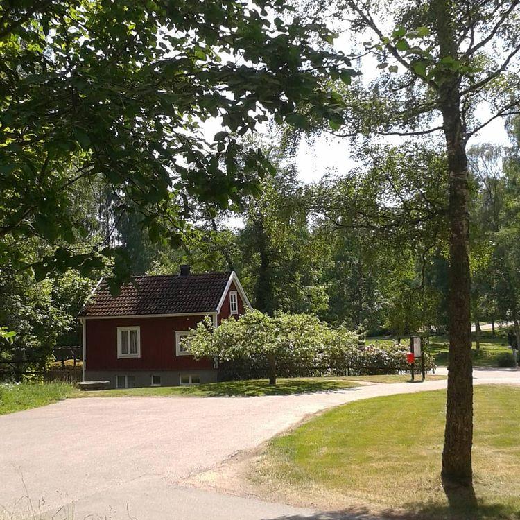Röd liten stuga på Skogskyrkogå - skogskyrkogardar | ello