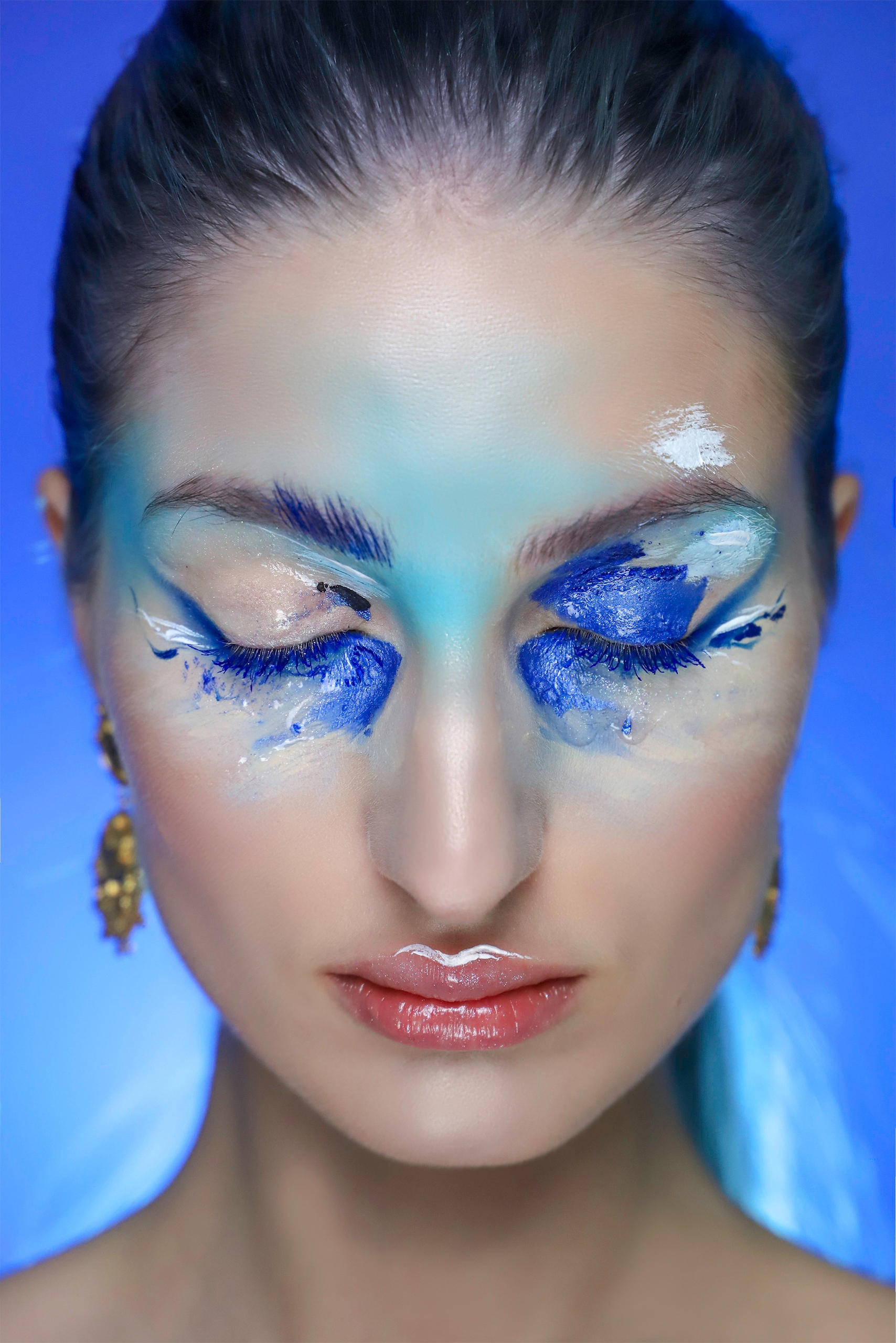 Fotografia przedstawia zbliżenie na artystyczny makijaż w niebieskiej tonacji. Kobieta na zdjęciu ma zamknięte oczy.
