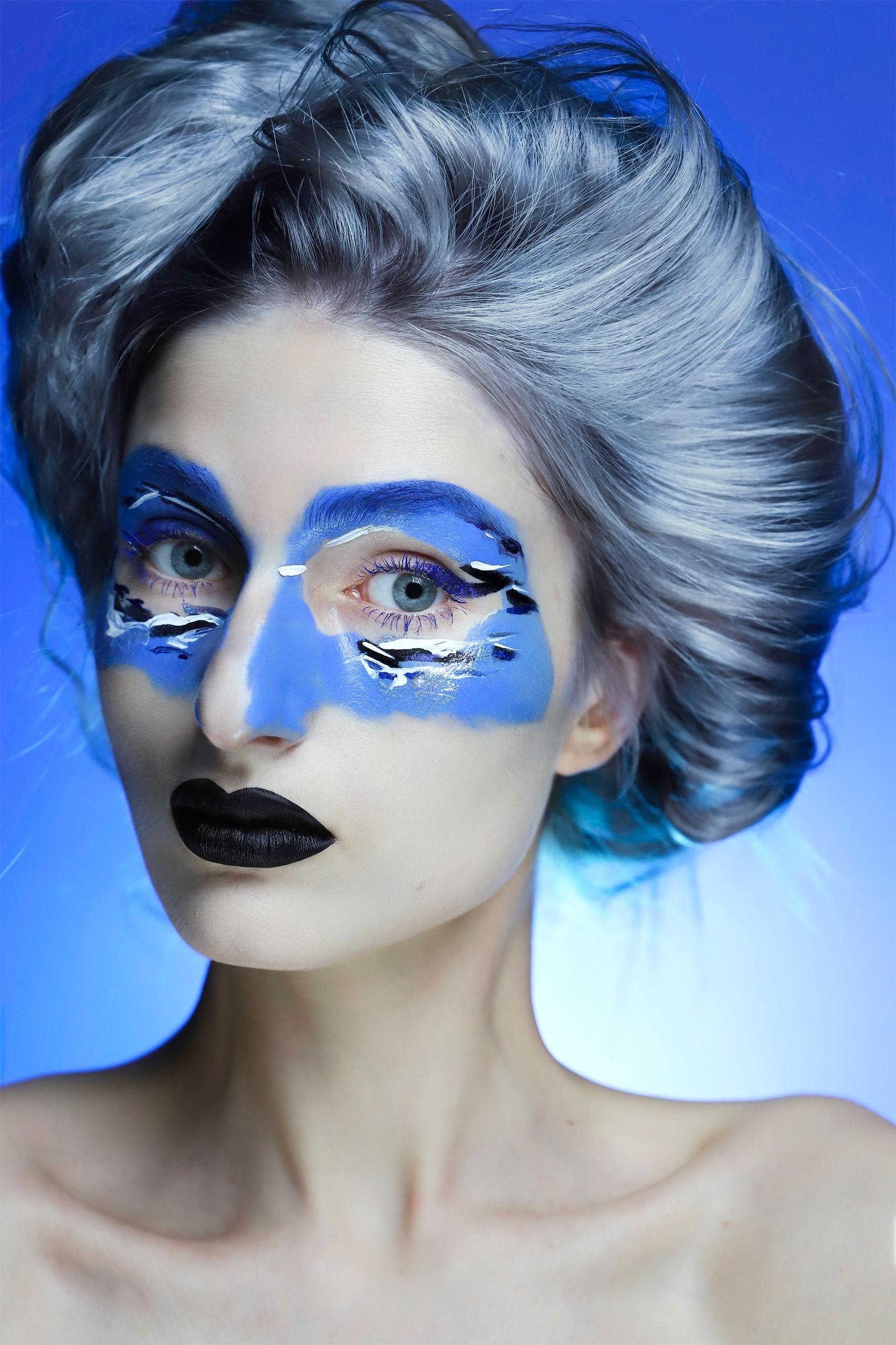 Fotografia przedstawia portret kobiety z szarymi włosami i czarnymi ustami na niebieskim tle.