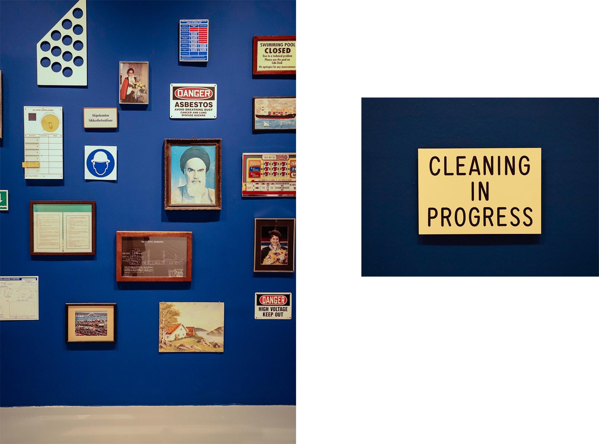 Obraz przedstawia zdjęcie ciemno-niebieskiej ściany, na której zawieszone jest dużo obrazków w różnych formatach.